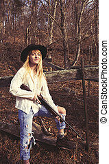 Young blond woman holding a gun standing in the woods