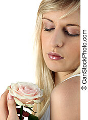 Young blond woman holding a rose