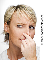 smell - young blond woman holding her nose because of a bad...