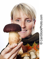 young blond woman holding mushrooms close up