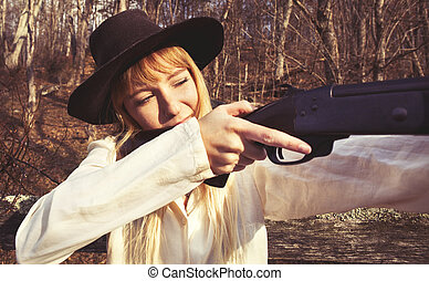 Young blond woman holding up a gun in the woods