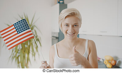 Young blond woman holding USA flag and showing thumbs up. Election and voting rights