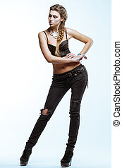 Young blond woman in black top and jeans posing on light background in studio