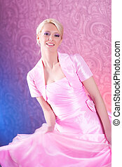 Young blond woman in pink dress dancing
