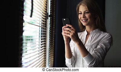 Young blond woman in white shirt using cell phone while standing next to a window