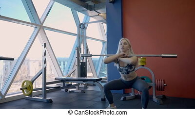 Young blond woman is doing barbell squats in moderm gym with big window.
