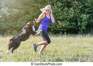 Young blond woman is running with her dog