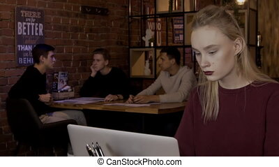 Young blond woman is writing email on her laptop in cozy cafe.