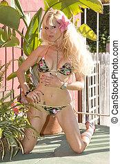 Young Blond Woman kneeling in a Bikini