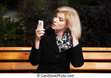 Young blond woman looking at mobile phone