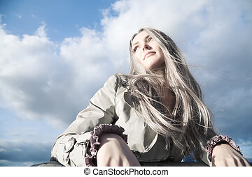Young blond woman on blue sky background