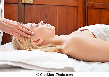 Young blond woman receiving head massage