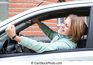 Young blond woman shaking hers fist sitting in vehicle