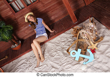 Young blond woman sitting near wooden house on a beach