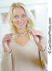 Young blond woman trying on some glasses