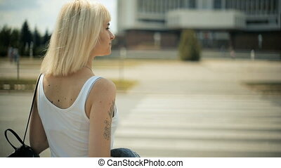 Young blond woman waits for cars to pass going to cross the road red light a crossing Back view