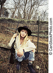 Young blond woman wearing hat siting in the woods with a gun