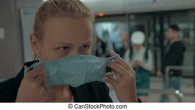 Young blond woman wearing surgical mask in the entrance of clinic. Hong Kong, China