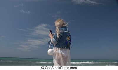 young blond woman with a smartphone in hand against the background of the sea and blue sky Slow motion