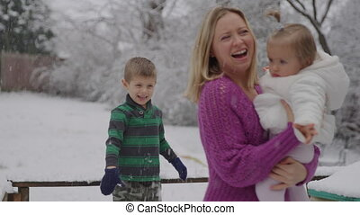Young blond woman with her kids enjoying in snow park
