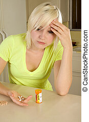 Young blond woman with medicine pills - Caucasian woman by...