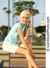 Young blond woman with short hair smiling outside
