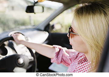 Young blond woman with sunglasses driving car.