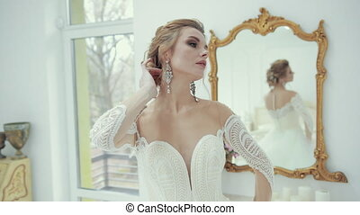 Young blonde bride in white wedding dress poses in front of camera, turns