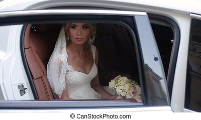 Young blonde bride sitting in car