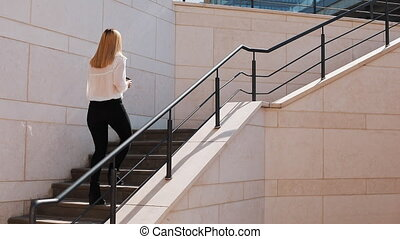 Young blonde business woman walks upstairs outside in a sunny day near office building