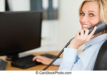 Young blonde businesswoman smiling into camera while on the...