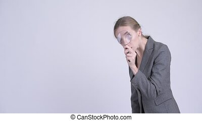 Young blonde businesswoman using magnifying glass - Studio...