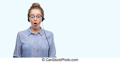 Young blonde call center operator woman scared in shock with a surprise face, afraid and excited with fear expression