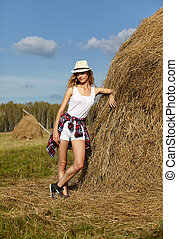 Young blonde country girl in hat near haystack
