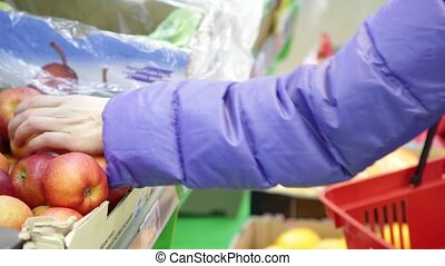 Blonde young woman choosing fruits at fruit vegetable supermarket marketplace.
