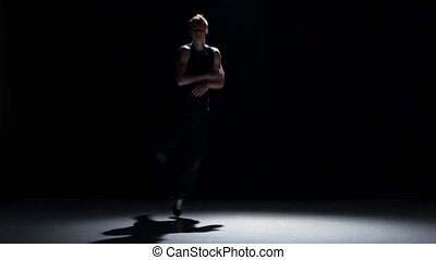 Young blonde dancer man dancing breakdance on black