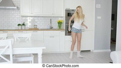 Young blonde dancing at home