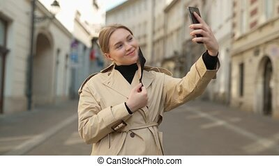 young blonde female tourist blogger takes selfie or make video call on empty street wearing a protective medical mask, covid 19 virus pandemic world quarantine, influenza danger