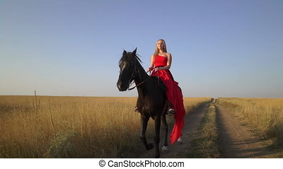 Young blonde girl horseback rider in red dress riding horse on country road
