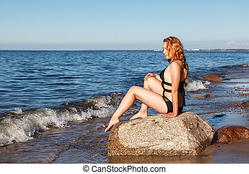 young blonde girl in a black bathing suit sits on a large stone of the sea