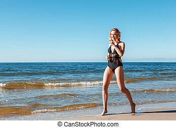 young blonde girl in a black swimsuit runs along the sand of the sea shore