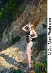 young blonde girl in a black swimsuit stands under a large cliff of the sea shore