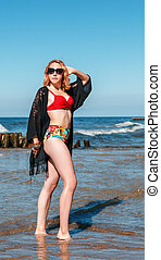 young blonde girl in a red swimsuit, sunglasses and black cape stands on the seashore
