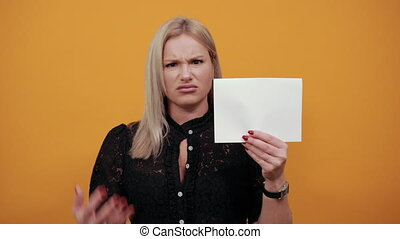 Young blonde girl in black dress on yellow background an irritated woman holds an empty sheet of paper in hand and demonstrate fingers