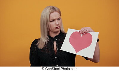 Young blonde girl in black dress on yellow background angry woman holds piece of paper with red heart in hand shoves finger in mouth