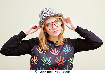 Young blonde girl in glasses touching her hat with hands