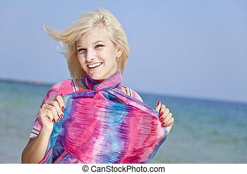 Young blonde girl in pink on the beach.