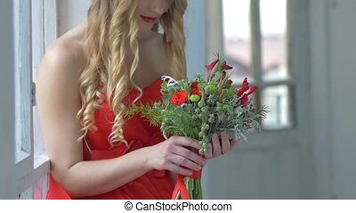 Young blonde girl in red dress smeling flowers, cam moves upwards, slow motion
