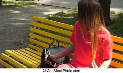 young blonde girl in red suit makes selfie at the park on a bench