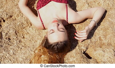 young blonde girl in red swimsuit sunbathing on the rock